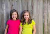Twin sisters with different hairstyle posing on wood fence — Stock Photo