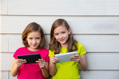 Twin sister girls playing with tablet pc happy on white wall — Стоковое фото