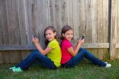 孪生妹妹玩智能手机坐在后院的草坪上的女孩 — 图库照片