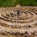 Atlantis spiral sign in Ibiza with stones on soil — Stock Photo