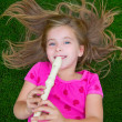 Blond kid children girl playing flute lying on grass — Stock Photo