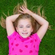 Beautiful blond kid children girl smiling lying on grass — Stock Photo