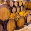 Stock Photo: Wine wooden oak barrels stacked in row at winery