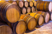 Wine wooden oak barrels stacked in a row at winery — Stock Photo
