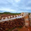 Masonry red stonewall in Menorca with fence door — Stock Photo
