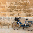 Bicycle in historical Ciutadellstone wall at Balearics — Stock Photo #35187891
