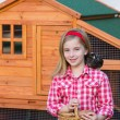 Breeder hens kid girl rancher farmer with chicks in chicken coop — Stock Photo #35693259
