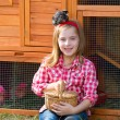 Breeder hens kid girl rancher farmer with chicks in chicken coop — Stock Photo #35694231