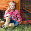 Breeder hens kid girl rancher farmer with chicks in chicken coop — Stock Photo #35694381
