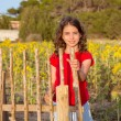 Smiling farmer girl with sunflowers field holding fence door — Stock Photo