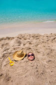 Funny girl playing buried in beach sand smiling sunglasses — Stock Photo
