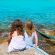 Blond and brunette kid girls sitting on beach port — Stok fotoğraf