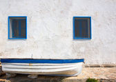 Mediterranean boat and whitewashed wall in white and blue — Stock Photo