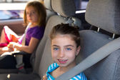 Kid girls with safety belt in car indoor — Stock Photo