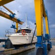 Stock Photo: Boat wheel crane elevating motorboat to yearly paint