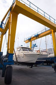 Boat wheel crane elevating motorboat to yearly paint — Stock Photo