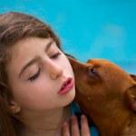 Brunette kid girl and dog pet whispering ear — Stock Photo #36823767