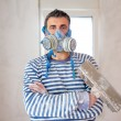 Funny plastering man mason with protective mask and trowel — Stock Photo