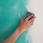 Plastering man hand sanding the plaste in drywall seam — Foto Stock