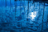 Blue water reflection of sailboats boats poles in waves — Stock Photo