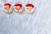 Christmas cookies with santa face on white fur background — Stock Photo