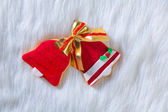 Christmas cookies red bell shape and ribbon on white fur — Stock Photo