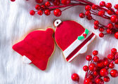 Christmas cookies red bell shape on white fur — Stock Photo