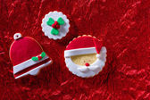 Christmas cookies Santa face and Xmas bell on red background — Stock Photo
