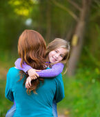 Mum holding daughter kid girl in her arms rear view smiling — Stock Photo