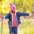 Stock Photo: Hiking kid girl with backpack pointing finger in autum forest
