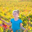 Stock Photo: Kid girl in autumn vineyard field holding red grapes bunch