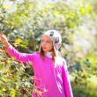 Stock Photo: Kid winter girl picking berries in forest