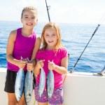 Happy tuna fisherwomen kid girls with fishes catch — Stock Photo