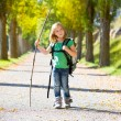 Blond explorer kid girl walking with backpack in autumn trees — Stock Photo #37655327