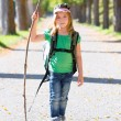 Blond explorer kid girl walking with backpack in autumn trees — Stock Photo #37655437