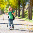 Blond explorer kid girl walking with backpack in autumn trees — Stock Photo #37655471