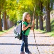 Blond explorer kid girl walking with backpack in autumn trees — Stock Photo #37655537