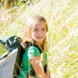 Stock Photo: Blond explorer kid girl walking with backpack in grass
