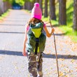Stock Photo: Hiking kid girl with walking stick and backpack rear view