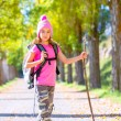 Hiking kid girl with walking stick and backpack in autumn — Stock Photo