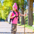 Stock Photo: Hiking kid girl with walking stick and backpack in autumn