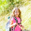 Stock Photo: Explorer kid girl walking with backpack in grass
