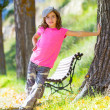 Stock Photo: Kid girl with camouflage pants and cap in park bench outdoor