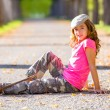 Autumn kid girl with camouflage pants sitting in trees track — Stock Photo