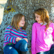 Sister kid girls smiling sit relaxed in a oak tree trunk — Stock Photo