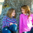 Stock Photo: Sister kid girls smiling sit relaxed in oak tree trunk
