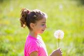 Kid girl looking dandelion flower in green meadow — Stock Photo