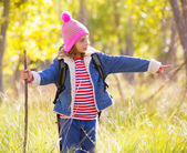 Hiking kid girl with backpack pointing finger in autum forest — Foto Stock