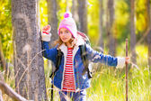 Hiking kid girl with backpack in autum poplar forest — Stock fotografie