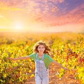 Kid farmer girl running in vineyard field in autumn — Stock Photo